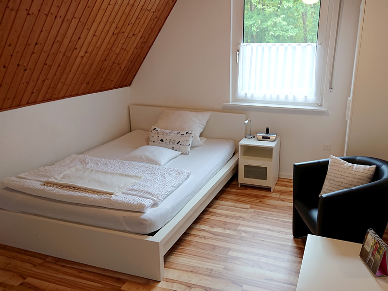 Ansicht 1 des 1. Schlafzimmers im OG zeigt Bett, Nachttisch und Sitzgelegenheit