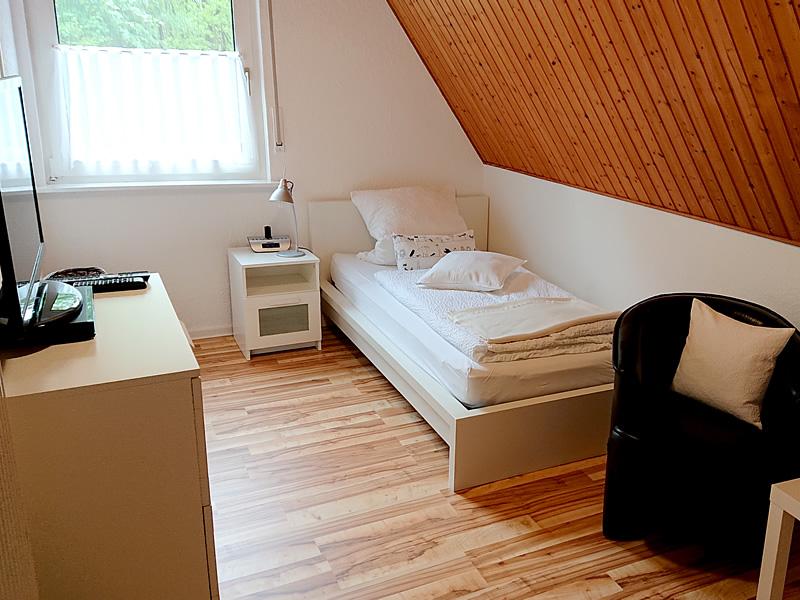 Ansicht 1 vom 2. Schlafzimmer im OG zeigt 140er Bett, Kommode und Sitzgelegenheit.