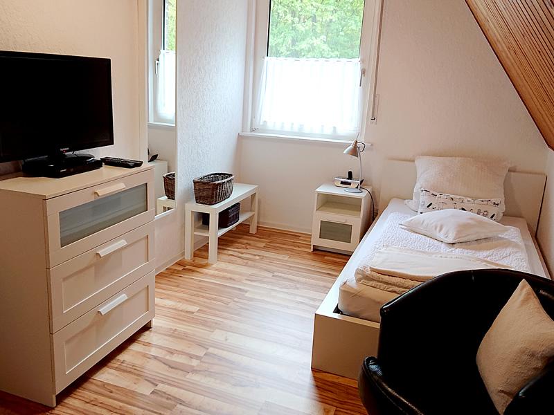 Ansicht 2 vom 2. Schlafzimmer im OG zeigt Kleiderschrank, Bett und Sitzgelegenheit.