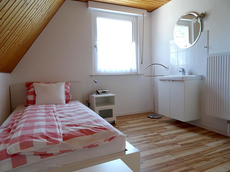 Ansicht 1 vom 3.Schlafzimmer im OG des Ferienhauses zeigt 140er Bett, Kleiderständer und Waschmöglichkeit.