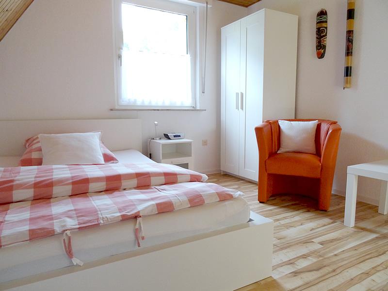 Ansicht 2 des 1. Schlafzimmers im OG zeigt Kleiderschrank, Sitzgelegenheit und Ankleidespiegel
